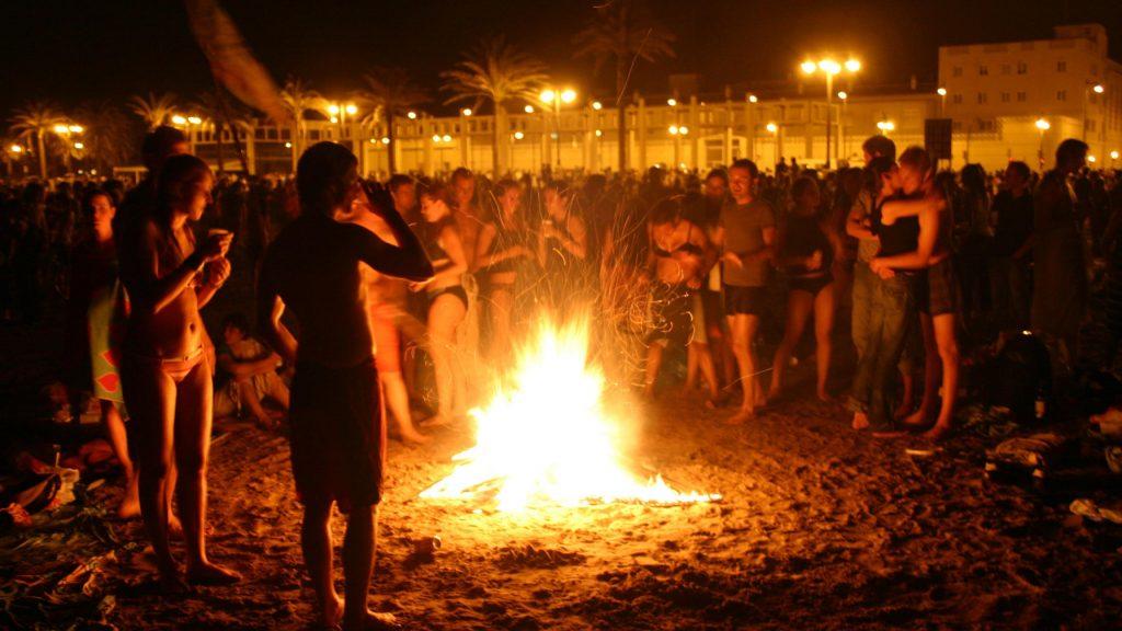 <em>Locals gather around bonfire in Valencia on San Juan.</em>
